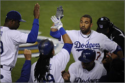 The Dodgers' Matt Kemp is congratulated by his teammates after hitting a first-inning home run.