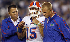 Florida quarterback Tim Tebow is escorted off the field by Gators personnel after suffering a concussion against Kentucky on Sept. 26.