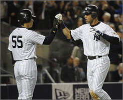 The Yankees' Derek Jeter, right, is greeted by Hideki Matsui after he scored on an Alex Rodriguez single to go up 4-2 in the fifth inning.