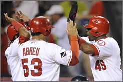 The Angels' Torii Hunter, right, is congratulated by teammates Erick Aybar and Bobby Abreu after hitting a three-run homer.