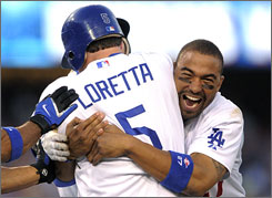 The Dodgers' Matt Kemp, right, congratulates Mark Loretta after his game-winning base hit.