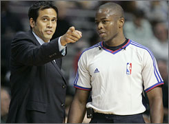 Heat coach Erik Spoelstra, left, talks with referee Ken Washington during the first half of an exhibition game against the Pistons on Wednesday.