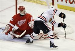 Detroit Red Wings goalie Chris Osgood stops the Blackhawks' John Madden's shot during the third period. Osgood made 31 saves Thursday in the rematch of the Western Conference finalists.