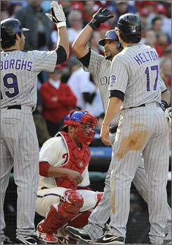 Rockies' Yorvit Torrealba is congratulated at home by Todd Helton (right) and Ryan Spilborghs (left) following his two-RBI home run against the Phillies in Game 2 of the NLDS.