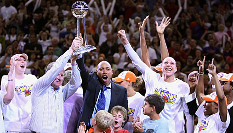 Owner Robert Sarver and coach Corey Gaines lift the trophy and celebrate with Mercury players after Phoenix won its second WNBA title in three years.