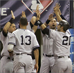 The Yankees' Jorge Posada, right, celebrates with teammates after hitting a solo home run in the seventh inning.