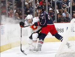 Calgary's Fredrik Sjostrom tries to control the puck while taking a hit from Rostislav Klesla of Columbus. The Blue Jackets beat the Flames 2-1.