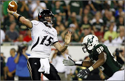 Cincinnati quarterback Tony Pike, pressured by South Florida's Aaron Harris during the first half, threw for two touchdowns before leaving the No. 9 Bearcats' win with a sprained left wrist.
