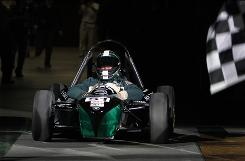"Michigan State basketball coach Tom Izzo makes his entrance in a race car during NCAA college basketball midnight madness festivities. ""Now that I know what it's like to drive an Indy car, I just hope I know what it's like to play again in Indianapolis, the city,"" he said."
