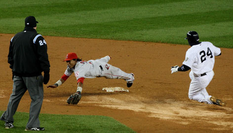 The Yankees' Robinson Cano runs to second base on a throwing error by Angels second baseman Maicer Izturis, not pictured, which Erick Aybar reaches for in the bottom of the 13th inning of Game 2 of the ALCS. The winning run scored on the play.