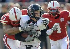 Texas Tech quarterback Steven Sheffield, center, is tackled by Nebraska's Ndamukong Suh, left, with Nebraska's Larry Asante, right, looking on during the first half of their game in Lincoln, Neb. Texas Tech pulled off the upset 31-10.