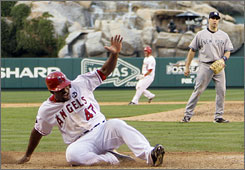 Howie Kendrick slides home with the winning run in front of the Yankees' Mark Teixeira on Jeff Mathis' double.