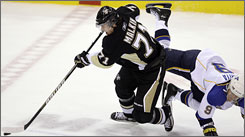 St. Louis' Paul Kariya, right, gets tangled up with Pittsburgh's Evgeni Malkin. The Penguins star tied a career best with 12 shots.