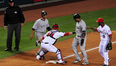 Angels catcher Mike Napoli tags out Robinson Cano and Jorge Posada, left, in the fifth inning as third baseman Chone Figgins looks on. Both were off the bag, but third-base umpire Tim McClelland called only Posada out.