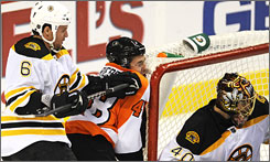 Boston's Dennis Wideman checked Danny Briere's into the goal during the third period.