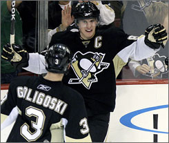 The Penguins' Sidney Crosby celebrates his game-tying goal in the third period against the Panthers with teammate Alex Goligoski. Crosby scored the lone goal in the shootout as Pittsburgh won its seventh game in a row.