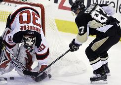 Pittsburgh Penguins' Sidney Crosby (87) can't get a stick on the puck as New Jersey Devils goalie Martin Brodeur makes the save in the first period of their game in Pittsburgh. The Devils beat the Penguins 4-1, ending Pittsburgh's 7-game winning streak.