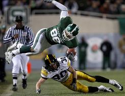 Michigan State's Brian Linthicum is upended by Iowa's Kyle Spading during the second quarter of their matchup in East Lansing, Michigan. Iowa won 15-13.