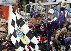 Denny Hamlin hoists the checkered flag in victory lane after posting his second Martinsville Speedway win.