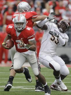 Ohio State quarterback Terrelle Pryor (2) rushes as teammate offensive lineman J.B. Shugarts (76) blocks Minnesota defensive end Cedric McKinley (55) Saturday.