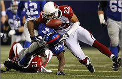 Arizona's Matt Ware, top, forces the Giants' Ahmad Bradshaw to fumble in the fourth quarter of the Cardinals' 24-17 victory in New York Sunday night. The Cardinals forced four Giants turnovers in the game.