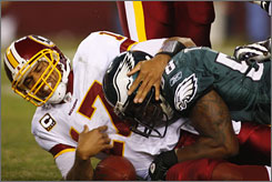 Redskins QB Jason Campbell falls victim to one of six sacks the Eagles recorded on Monday night.
