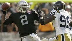 New York Jets linebacker Bryan Thomas, right, pressures Oakland Raiders quarterback JaMarcus Russell into throwing an incomplete pass during their game in Oakland.