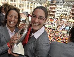 German national team players Birgit Prinz, right, and Inka Grings, left, hold the European trophy as the team celebrates on the balcony of the town hall Sept. 11 in Frankfurt, Germany, the day after beating England 6-2 in the final.