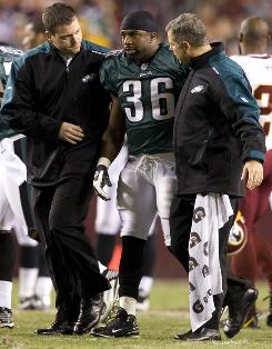 The Eagles' Brian Westbrook, center, is led off the field after suffering a concussion in the first quarter of Monday night's game against the Redskins.