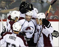 Wojtek Wolski, center, is congratulated by Colorado teammates after he scored what turned out to be the game-winning goal in the third period of the Avalanche's 3-2 win over Calgary on Wednesday.