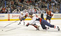 Washington Capitals defenseman Milan Jurcina, right, dives to knock the puck off the stick of Atlanta Thrashers right wing Maxim Afinogenov in the second period at Philips Arena in Atlanta.  The Capitals beat the Thrashers 4-3.