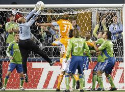 Seattle goalkeeper Kasey Keller snares the ball under pressure.