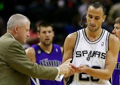 A team official, left, applies hand sanitizer for San Antonio Spurs player Manu Ginobili's hands after the Spurs guard swatted a rogue bat from the air and removed it from the court during the first half of the game against the Sacramento Kings in San Antonio. The Spurs beat the Kings 113-94.