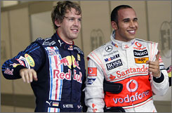 McLaren's Lewis Hamilton, right, winks at the crowd as he stands with second-fastest qualifier Sebastian Vettel in the paddock of the Yas Marina course.