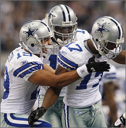 Dallas' Miles Austin, left, and Roy Williams. center, congratulate teammate Sam Hurd after his first quarter touchdown.