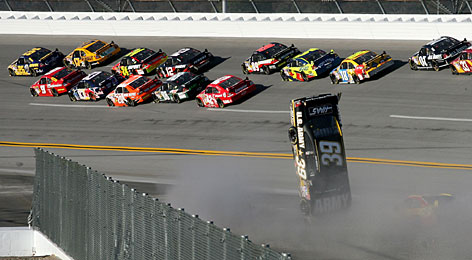 The back of Ryan Newman's car lifts off the ground in a multicar wreck as Jamie McMurray (26) leads the main pack in the closing laps at Talladega Superspeedway.