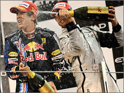Red Bull driver Sebastian Vettel gets the champagne treatment from F1 champ Jenson Button on the podium at the first Abu Dhabi Grand Prix.