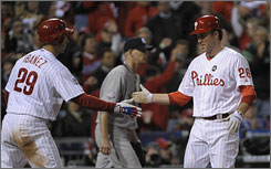 The Phillies' Chase Utley, right, is greeted by Raul Ibanez after scoring on Jayson Werth's third-inning single.