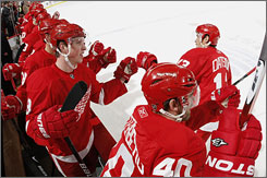 Pavel Datsyuk (two assists) celebrates Tomas Holmstrom's first-period goal with the Detroit bench.