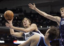 Mavericks forward Dirk Nowitzki goes to the basket against Utah Jazz forward Andrei Kirilenko, right, and Jazz center Mehmet Okur in the second half of their game in Dallas. Nowitzki scored a franchise-record 29 points in the fourth quarter to help the Mavs win 96-85.