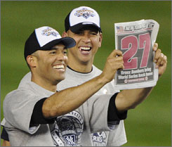 The Yankees' Mariano Rivera, left, and Alex Rodriguez check out a newspaper after the team's 27th world championship
