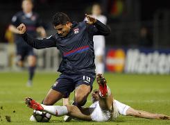 Liverpool's Javier Mascherano, bottom, tackles Lyon's Ederson on Wednesday.