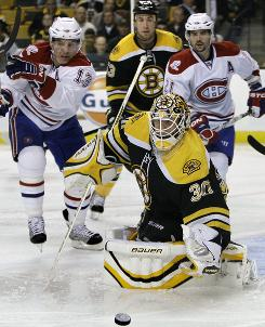 Boston Bruins goalie Tim Thomas (30) makes a save as he is pressured by Montreal Canadiens left wing Michael Cammalleri, left, and right wing Brian Gionta, right, during the second period of their NHL hockey game in Boston. The Canadiens beat the Bruins in a shootout 2-1.