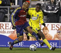The Columbus Crew's Emmanuel Ekpo, right, and Real Salt Lake's Robbie Russell chase a loose ball during the first half of the teams' MLS Eastern Conference playoff game Thursday in Columbus, Ohio. Real Salt Lake defeated Columbus 3-2, eliminating the Crew from the playoffs.