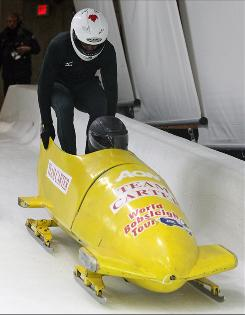 Jamaica two-man bobsled team brakeman Marvin Dixon, left, jumps into the team's rented sled as Hannukkah Wallace pilots during the FIBT International training week at the Whistler Sliding Centre in Whistler, British Columbia.