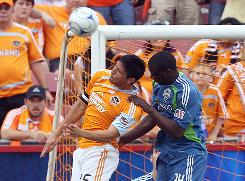 Houston's Brian Ching, left, and Seattle's Jhon Kennedy Hurtado go up for a header Sunday. Ching later scored the opening goal with a right-footed blast.