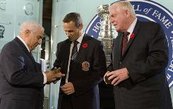 Hockey Hall of Fame Chairman Bill Hay, right, watches as Selection Committee Co-Chair Jim Gregory, left, puts the ring on Steve Yzerman's finger in a ceremony at the Hockey Hall of Fame in Toronto.