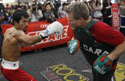 In a Nov. 4 photo, boxer Manny Pacquiao trains with Freddie Roach at the Wild Card Boxing Club in Los Angeles. Pacquiao is scheduled for a world welterweight championship boxing bout against Miguel Cotto on Nov. 14 in Las Vegas.