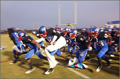 The Pahokee High School football team takes the field during a game on Sept. 4. The sport is a rallying point for the community's youth in Pahokee.