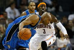 The Orlando Magic's Vince Carter, who was initially ruled out of Tuesday's game with an ankle injury, drives against Gerald Wallace of the Charlotte Bobcats during their teams' game in Charlotte.